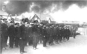 Treowen Road, August 1940. Tired firemen at roll call by Pennar School. Behind them, acrid smoke pours from the burning oil tanks.